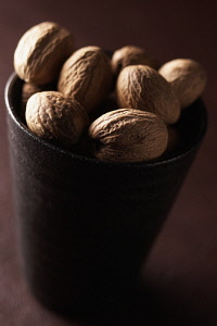 Nutmeg, Mace, Myristica fragrans, Mass of brown coloured spice in cup.
