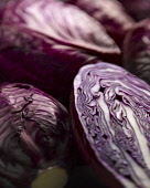 Cabbage, Red cabbage, Brassica oleracea capitata. A cut half among whole ones. Moody lighting.
