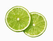 Lime. Citrus aurantiifolia, Plan view of two slices overlapping, cut out on white.