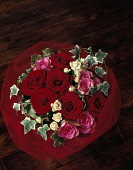 Rose, Rosa 'Passion',Overhead view of a bouquet of six red roses with six pink and white roses with variegated ivy, surrounded by a red net wrap.