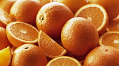 Orange, Citrus sinensis, Several whole fruits, with halves and quarters grouped together.