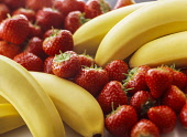 Banana, Musa acuminata, Two bunches with strawberries  grouped between.
