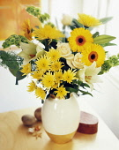 Chrysanthemum, yellow Gerberas, cream Roses and Easter lily, Lilium longifolium, with greenery in a vase on a small wooden table.
