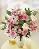 Lily, Lilium 'Star Gazer', Floral arrangement with pink chrysanthemum roses and carnations in a vase on a small table.