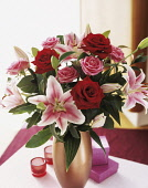 Lily, Lilium 'Star Gazer', Floral arrangement with pink and red roses in a vase on a small table.