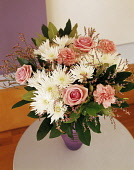 Daisy, White Chrysanthemum,  pink roses and carnations, fFloral arrangment with greenery in a vase on a small wooden table.