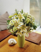 Lily, Lilium 'Star Gazer' white form, Floral arrangement with white chrysantemum and green carnations arranged in a vase on a small table.