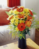 Daisy, Chrysanthemum, Floral arrangment with orange Gerberas, Roses and Oriental Lilies with greenery in a black vase on a small wooden table.
