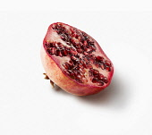 Pomegranate, Punica granatum, Side view of one fruit cut in half showing the juicy red seeds inside.