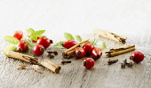 Rosehip, Rosa canina. Several hips arranged with leaves and pieces of cinnamon stick and cloves on pale, distressed, wooden background. Selective focus.