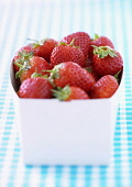 Strawberry, Fragaria x ananassa, Studio shot of red fruit in container.