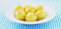 Lemon, Citrus limon, Mass of yellow coloured fruit in white bowl.